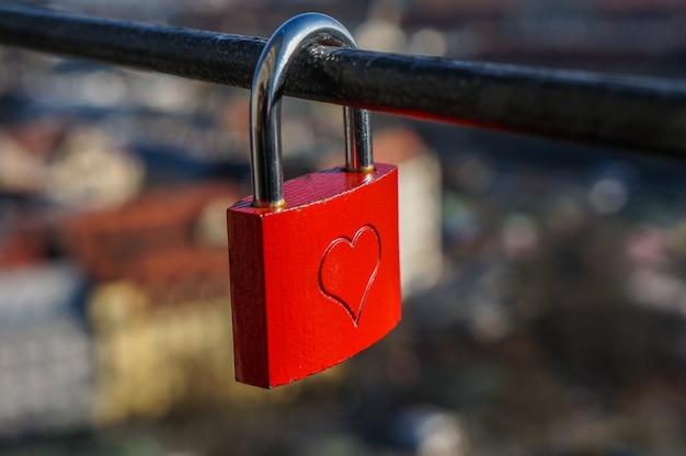 Serrure de mariage rouge avec coeur sur une main courante symbole du mariage