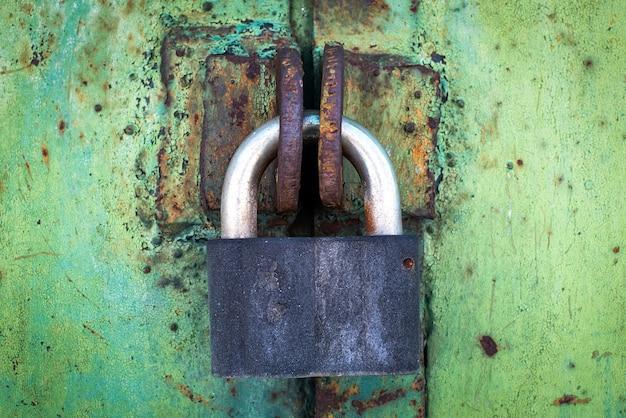 Serrure rouillée sur une texture de vieux, métal, fer, vert, porte céladon, dont l'ancienne peinture s'écaille. le passage est fermé. fermé à clé.