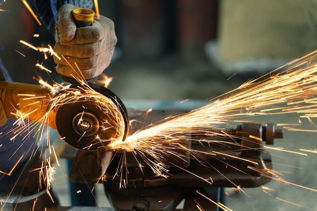 Serrurier dans des vêtements spéciaux et des lunettes travaille dans la production. traitement du métal avec meuleuse d'angle. des étincelles dans le travail des métaux.