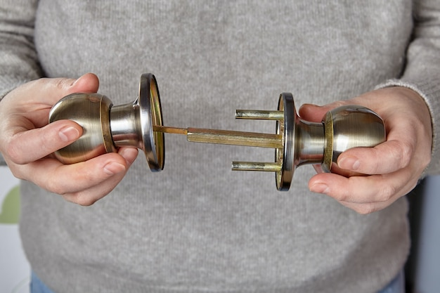 Le serrurier insère l'axe dans la poignée de la porte intérieure pour vérifier le fonctionnement du mécanisme de verrouillage.