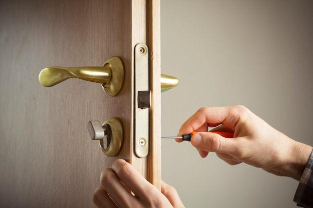 Serrurier installe la poignée de porte. réparer le verrouillage de la porte.
