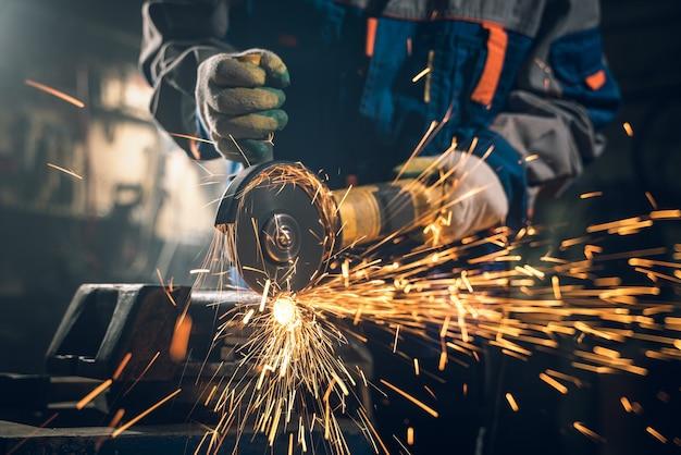 Serrurier en vêtements spéciaux et lunettes travaille en production. traitement du métal avec meuleuse d'angle