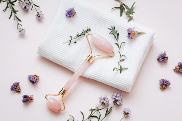 Sérum d'acide hyaluronique rose, rouleau de beauté en quartz rose, gua sha et fleurs violettes sur un plateau rose. cosmétiques et outils anti-vieillissement, espace de copie, vue de dessus