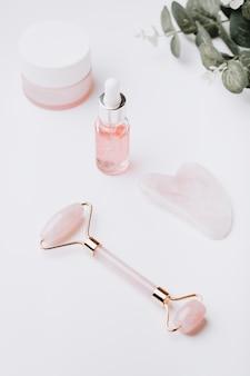Sérum d'acide hyaluronique rose, rouleau de quartz rose, gua sha et crème hydratante pour le visage sur un dessus de table blanc. cosmétiques et outils anti-vieillissement sur blanc, espace de copie, vue de dessus, bannière web