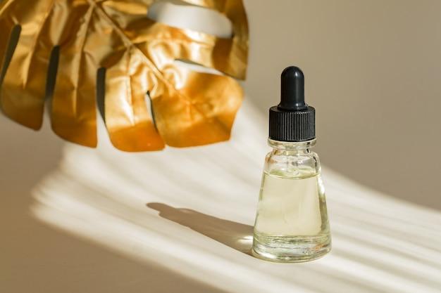 Sérum anti-âge avec pipette gouttes. feuille d'or monstera sur mur. bouteille professionnelle pour le soin du visage et du corps