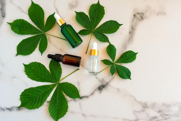Sérum aux extraits floraux pour le soin de la peau. concept de spa pour les soins du visage et du corps. cosmétiques nature dans une bouteille en verre avec une pipette et avec des feuilles vertes sur fond de marbre.