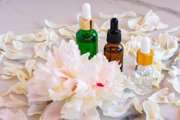 Sérum aux extraits floraux pour le soin de la peau. concept de spa pour les soins du visage et du corps. cosmétiques nature dans une bouteille en verre avec une pipette et avec des pétales de pivoine sur fond de marbre.