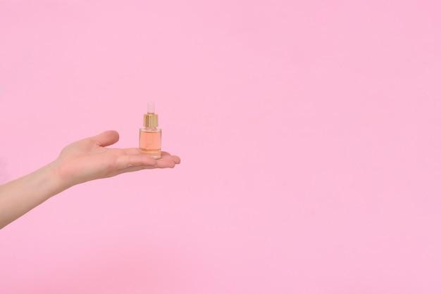 Sérum cosmétique en flacons compte-gouttes en verre transparent sur fond rose dans la main d'une femme. le concept de produits de soins naturels de la peau. produits de soins de la peau essence pour une belle peau saine.
