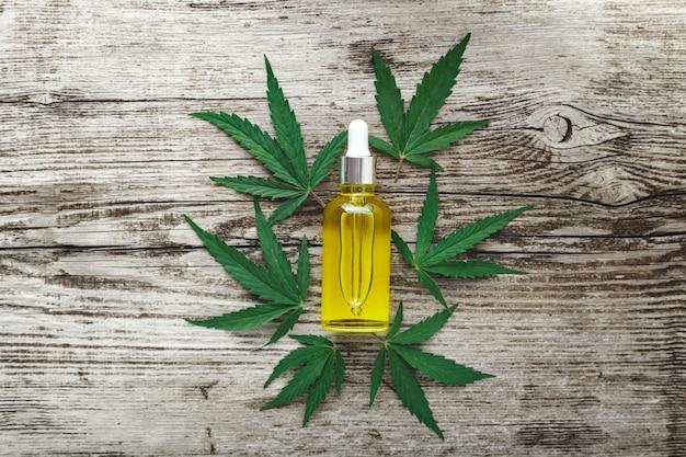 Sérum d'huile de cbd de chanvre dans un flacon compte-gouttes en verre sur des feuilles de cannabis. feuille de cannabis avec produit cosmétique de soin de la peau huile de cbd sur fond de bois ancien.