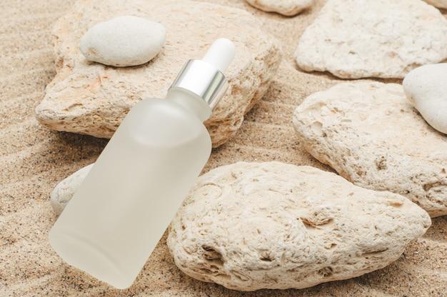 Sérum hydratant pour le visage sur la surface sablonneuse de la mer d'été avec des pierres