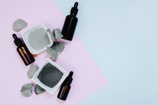Sérum pour hydrater la peau en flacon marron avec une pipette. feuilles d'eucalyptus à côté des produits hydratants et nettoyants pour la peau