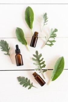 Sérum visage raffermissant et huiles essentielles biologiques sur fond de bois blanc avec feuilles de cinnar, chistets. mise à plat.
