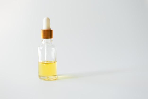 Sérum de vitamine d'huile dans une bouteille en verre sur un mur clair, copiez l'espace. produit de beauté pour la peau