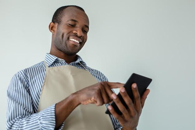 Serveur afro-américain positif souriant en se tenant debout contre le mur blanc