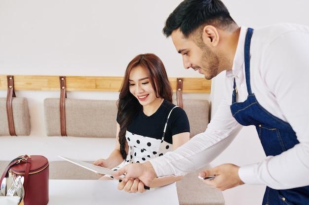 Serveur aidant le client avec le menu
