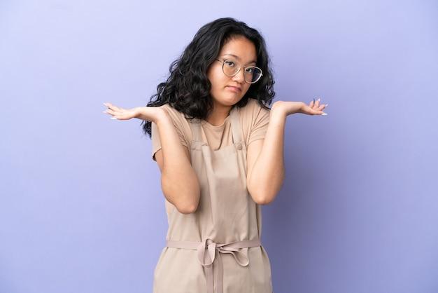 Serveur asiatique de restaurant isolé sur fond violet ayant des doutes en levant les mains