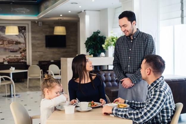 Serveur au service d'une famille dans un restaurant