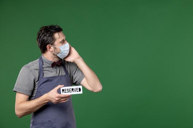 Serveur de banquet concentré en uniforme avec masque médical et montrant une icône réservée regardant quelque chose sur le côté gauche sur fond vert