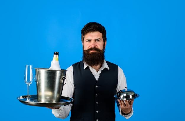 Serveur beau serveur avec plateau de service et serveur refroidisseur de vin au restaurant portant une cloche en métal