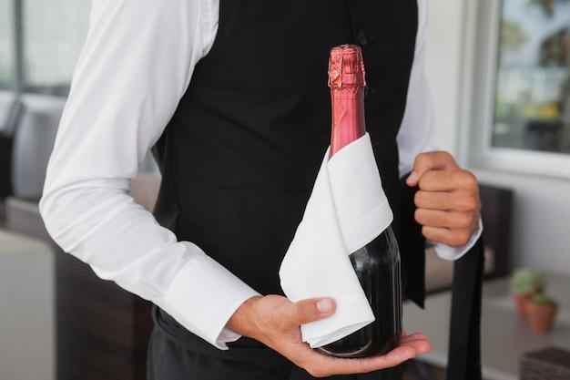 Serveur bien habillé tenant magnum de champagne