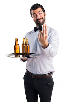Serveur avec des bouteilles de bière sur le geste du plateau