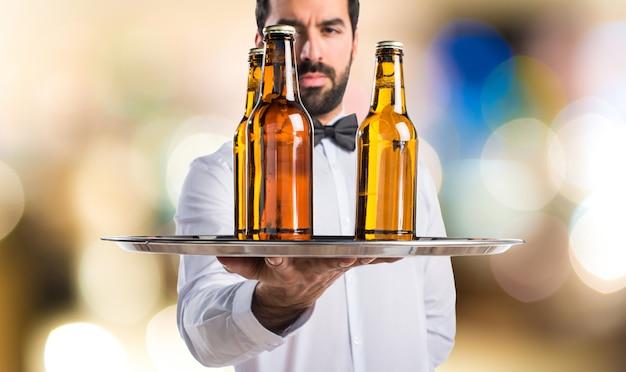 Serveur avec des bouteilles de bière sur le plateau en arrière-plan non focalisé