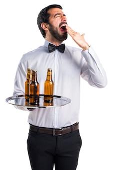 Serveur avec des bouteilles de bière sur le plateau bâillonnement