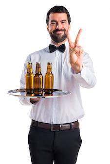 Serveur avec des bouteilles de bière sur le plateau en comptant deux