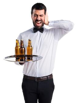 Serveur avec des bouteilles de bière sur le plateau couvrant ses oreilles