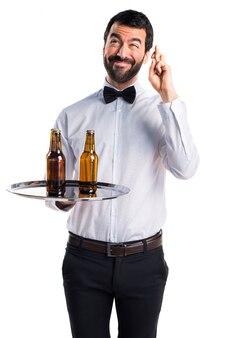 Serveur avec des bouteilles de bière sur le plateau avec les doigts croisés