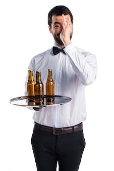 Serveur avec des bouteilles de bière sur le plateau en faisant une blague