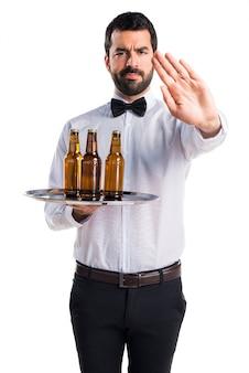 Serveur avec des bouteilles de bière sur le plateau faisant signe d'arrêt
