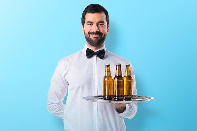 Serveur avec des bouteilles de bière sur le plateau sur fond coloré