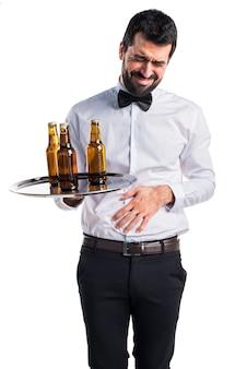 Serveur avec des bouteilles de bière sur le plateau avec mal au ventre