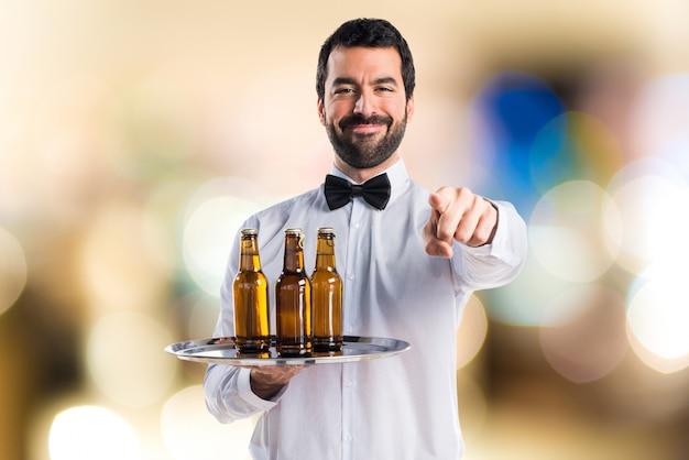 Serveur avec des bouteilles de bière sur le plateau pointant vers l'avant en arrière-plan non focalisé