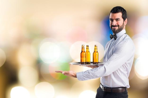 Serveur avec des bouteilles de bière sur le plateau présentant quelque chose en arrière-plan non focalisé
