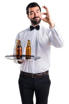 Serveur avec des bouteilles de bière sur le plateau en signant ok