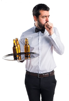 Serveur avec des bouteilles de bière sur le plateau toussant