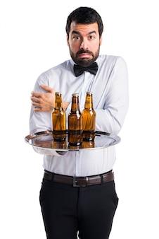 Serveur avec des bouteilles de bière sur le plateau en train de se figer