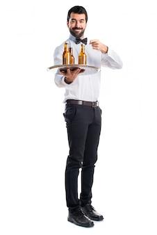 Serveur avec des bouteilles de bière sur le plateau