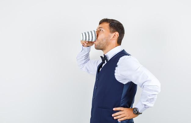 Serveur buvant une tasse de thé en chemise blanche, gilet bleu foncé.