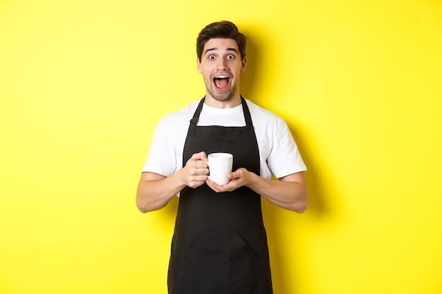 Serveur de café sympathique debout avec les mains levées, placez votre signe ou logo, debout sur fond jaune.