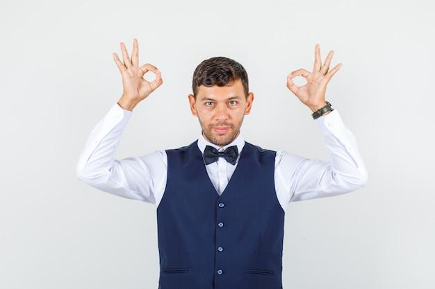 Serveur en chemise, gilet montrant le signe ok et à la vue de face, joyeuse.