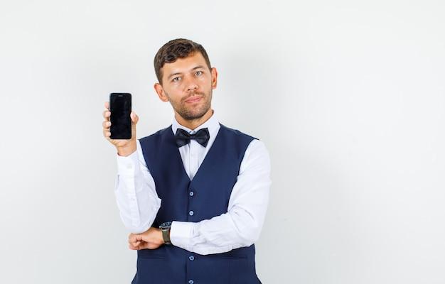 Serveur en chemise, gilet tenant le téléphone mobile et à la vue de face, confiant.