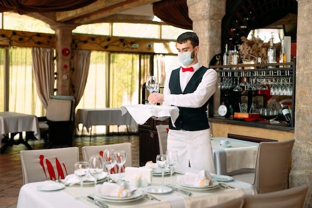 Un serveur dans un masque de protection médicale sert la table dans le restaurant.
