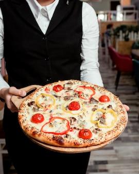 Serveur détient une pizza à la viande avec des poivrons rouges jaunes tomate et fromage