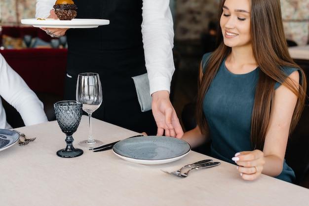 Un serveur élégant en tablier sert une jeune fille dans un bon restaurant. service clients.