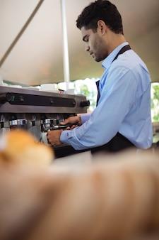 Serveur faisant une tasse de café à partir d'une machine à expresso