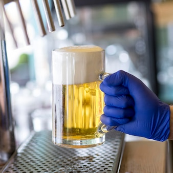 Serveur de gros plan avec des gants et chope de bière