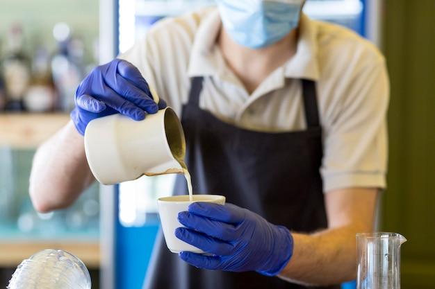 Serveur de gros plan avec des gants, préparer le café
